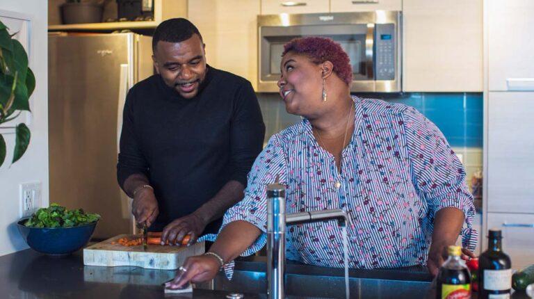 black couple cooking vegetables together