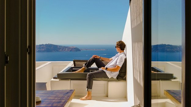 man in white shirt sits outside of a luxury house in front of the sea