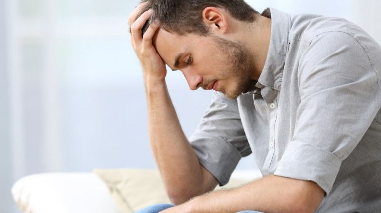 A sad man with a hand on the head sitting on a couch in the living room at home   Feature   Male Depression - How To Get Back To Feeling Like Yourself Again