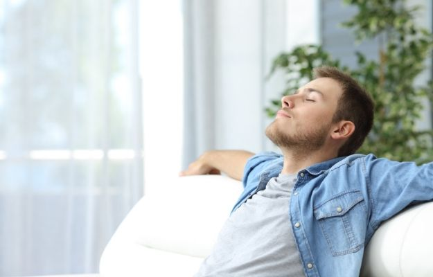 Portrait of a casual tired man resting sitting on a couch at home | Improved Wellness | Get Clarity | How Clarifying The Mind Can Boost Your Health