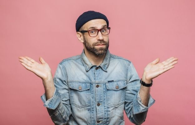 a man is confusing and hesitation with arm opened with pink background |