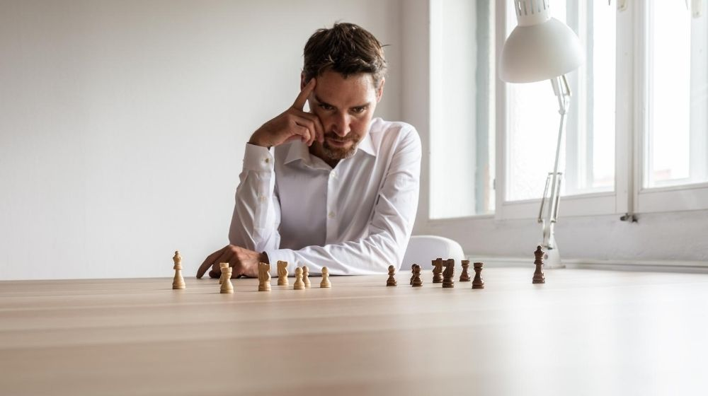 a man playing chess and try to make decision with a lamp next to chesses | feature | How To Strengthen Your Decisiveness Ability