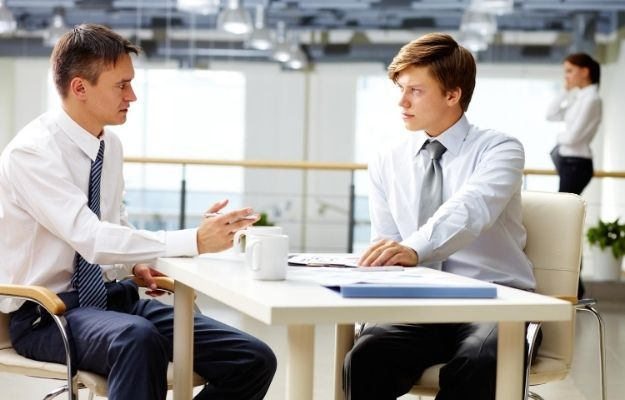 two men are talking with folders on the table with a girl calling behind | Consider Asking For Help From A Life Coach | How To Strengthen Your Decisiveness Ability