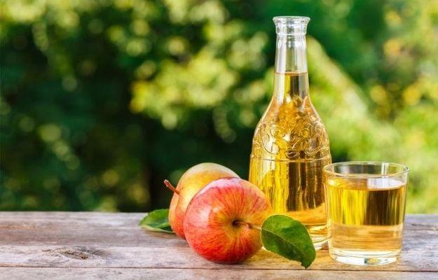 Apple Cider Vinegar bottle and 2 apples with garden background | What Is Apple Cider Vinegar? | Can Apple Cider Vinegar Help Treat Erectile Dysfunction?
