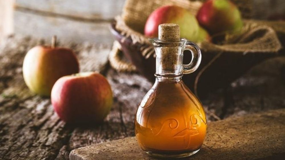 Apple Cider Vinegar bottle with apples in the background | Feature | Can Apple Cider Vinegar Help Treat Erectile Dysfunction?