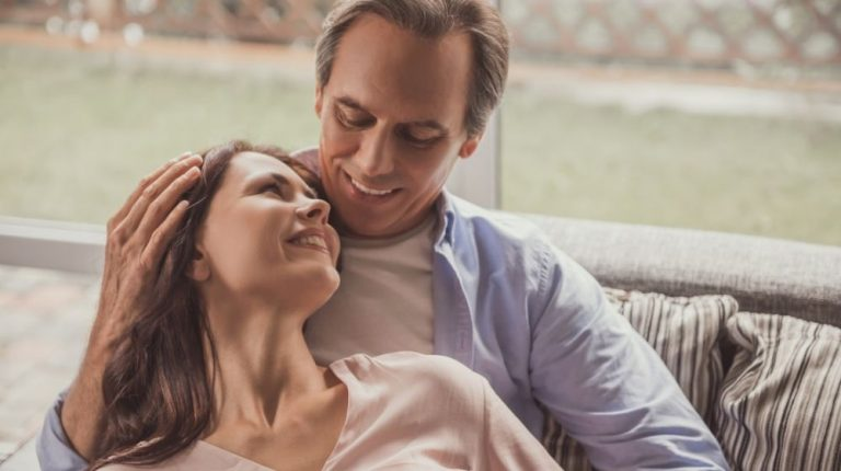 Beautiful couple is hugging and smiling while resting on couch at home