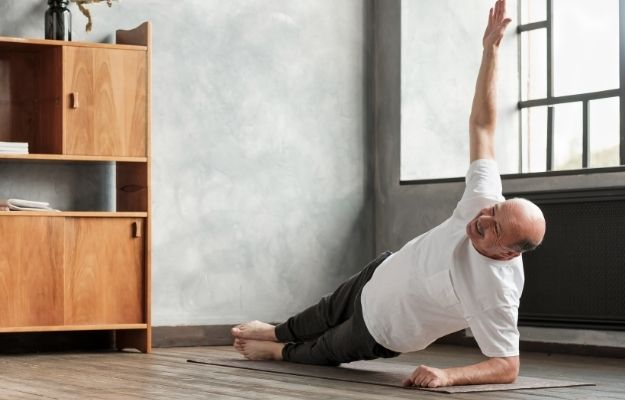 Cheerful senior hispanic man doing a side plank exercise at living room | Keep Moving | Maintain Your Physical Vitality with These 5 Life Hacks