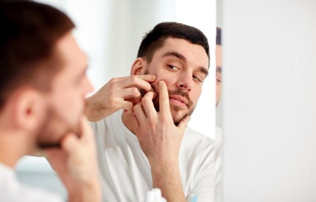 man looking in the mirror and squeezing the acne | Common Causes of Acne in Adult Men | How to Treat Acne in Men Fast