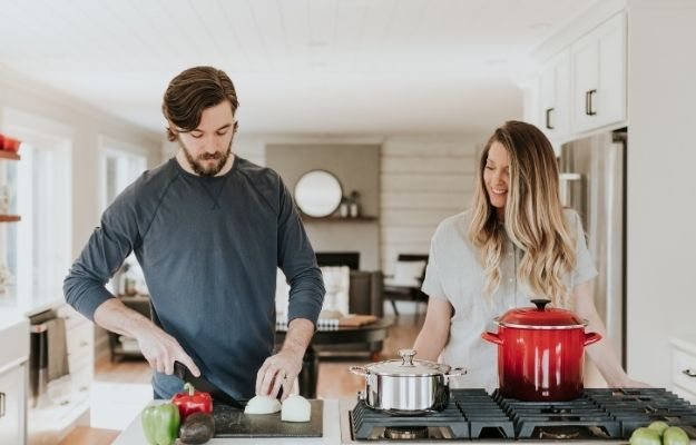 man slicing onion standing beside smiling woman | The Benefits of Reducing Red Meat and Increasing Plant Protein | Live Like a Rock Star (and Still Be Healthy)