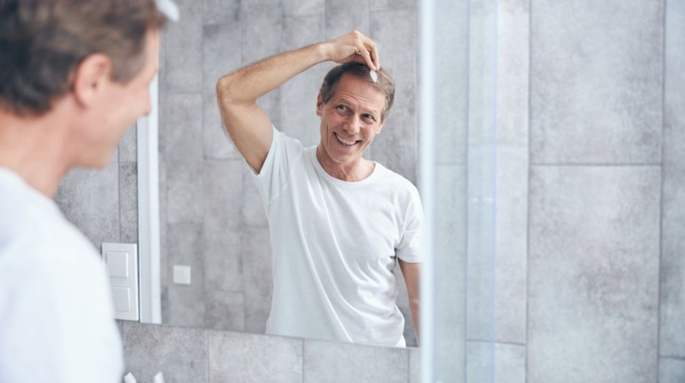middle-aged man is combing his hair in front of mirror | Feature | 7 Tips & Tricks To Deal With Receding Hairline In Men