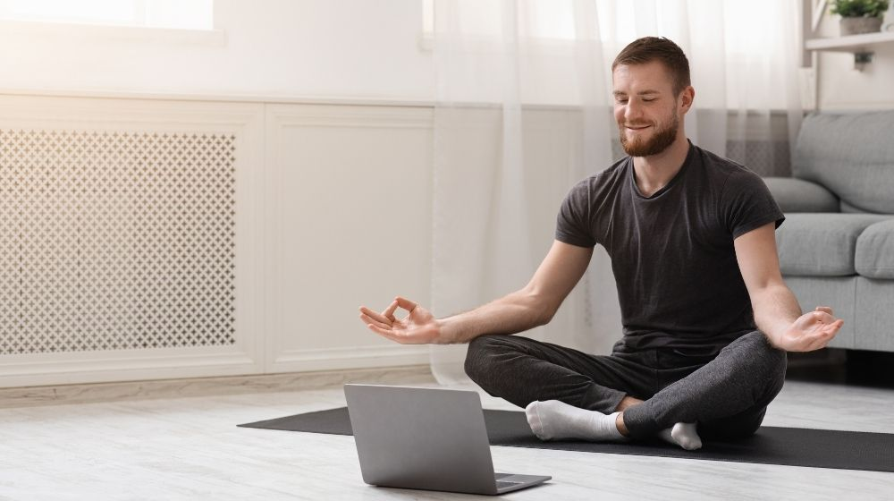 a guy meditating with trainer online via laptop connection | Feature | When Is The Best Time To Meditate For Optimized Health?