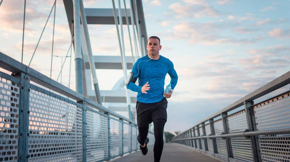 athletic-middle-aged-man-running-on-bridge