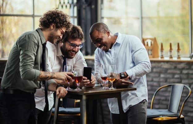 group of man grabbing a drink and laughing together after work-ca