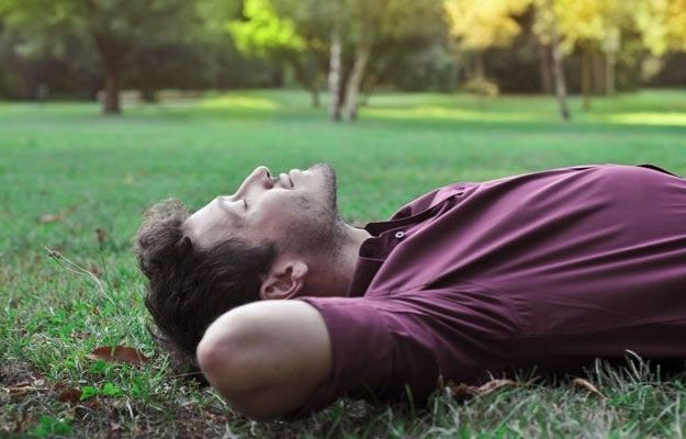 man lying on grass and practicing mindfulness | The Benefits of Meditation | When Is The Best Time To Meditate For Optimized Health?