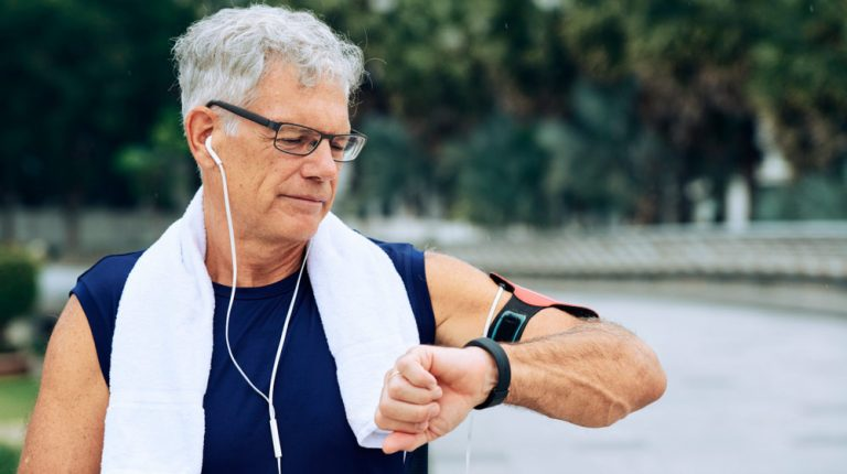 mature-man-looking-at-smart-watch-during-workout