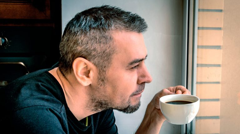 middle-aged-man-looking-out-the-window-with-a-cup-of-coffee | How To Have More Energy In The Morning
