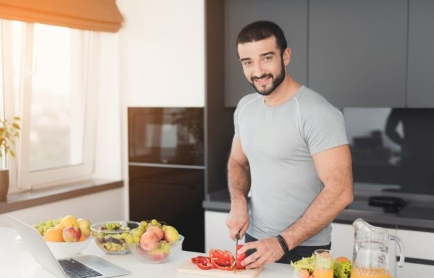 happy man is sliding tomatoes in kitchen | The Bottom Line | Benefits of Fenugreek for Testosterone