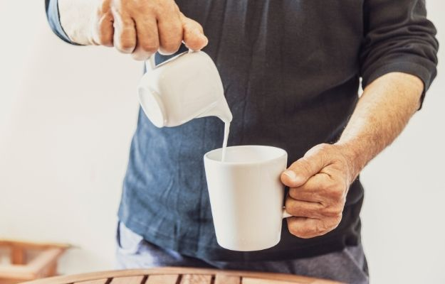 man is pouring milk in white cup | Benefits of Spermidine for Cell Renewal