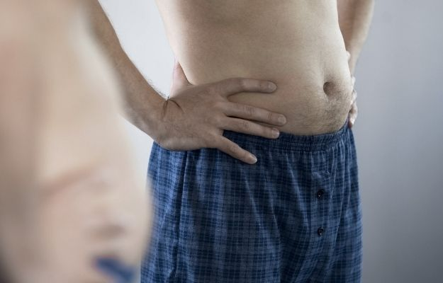 Aged man looking at his belly in the mirror | Common ED Causes, Symptoms, and Treatments