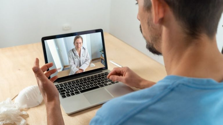 Back view of man making video call with his doctor - featured photo - ss | What is Telehealth? And What Are The Benefits | featured