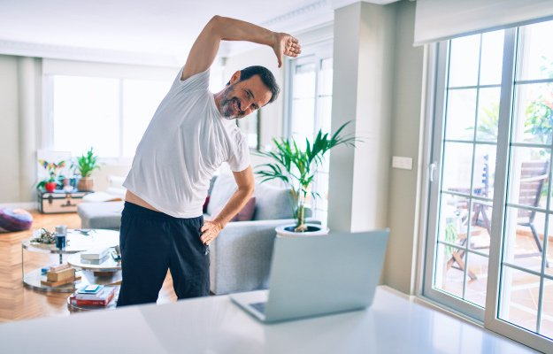 Middle age man with beard training and stretching doing exercise at home looking at sport video on computer | Men's Path to Improved Health | Benefits of Preventive Health Care