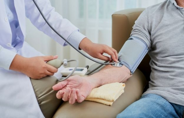 a doctor measuring blood pressure of senior man sitting in couch | Do Not Shy Away From a Doctor | 5 Top Male Health Concerns and What You Can Do