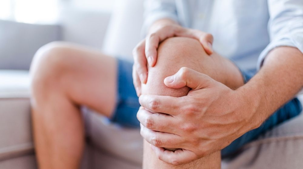a man is holding his knee | Feature | 5 Knee Strengthening Exercises to Beat Knee Pain