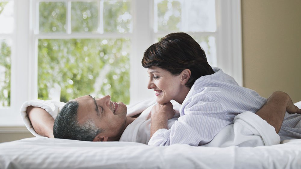 Side view of happy woman looking at husband while lying in bed   Feature   Getting To Know The P Spot (Male G-Spot)