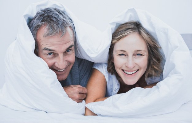Happy middle aged couple under the duvet smiling at camera in bedroom at home | Low Testosterone Symptoms in Men
