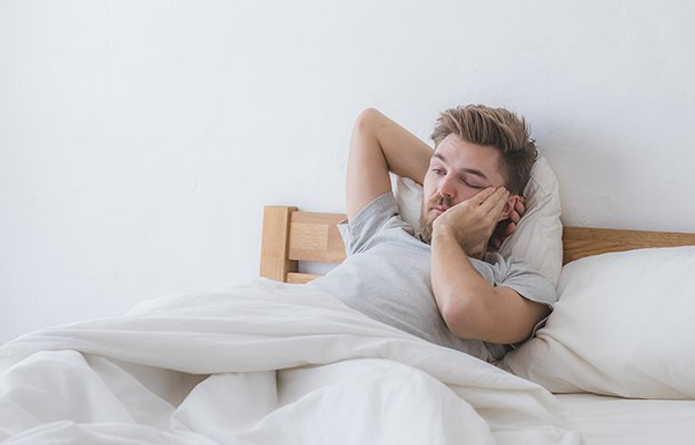 man feeling tired and misaligned sleeping pattern because of sleeping in | Is Sleeping In Bad For Your Sleep Routine or Health