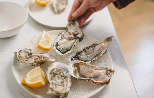 A dish full of raw oysters | Eat These 7 Foods To Boost Testosterone Naturally