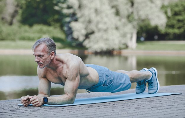 Concentrated muscle bound mature man with shirt doing plank on exercise mat near river | 5 Simple Exercises for Building Muscles