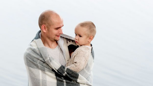 bald-father-holding-infant-son-in-arms-under-big-scarf-ss-alopecia   Male Pattern Baldness Symptoms & FAQ