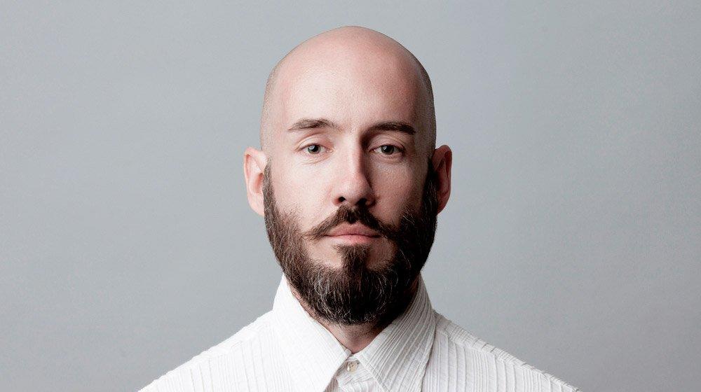 confident-bald-middle-aged-man-studio-shot-on-grey-background