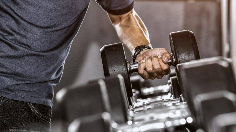 Strong-well-built-bodybuilder-lifting-dumbbell-weights | The Benefits of Strength Training in Your 40's and 50's | feature