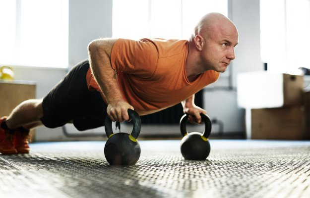bald-middle-aged-sportsman-standing-in-plank-position-with-help-of-kettlebells-----------ENERGY-AND-FOCUS-----------_body | The Benefits of Strength Training in Your 40's and 50's | ENERGY-AND-FOCUS