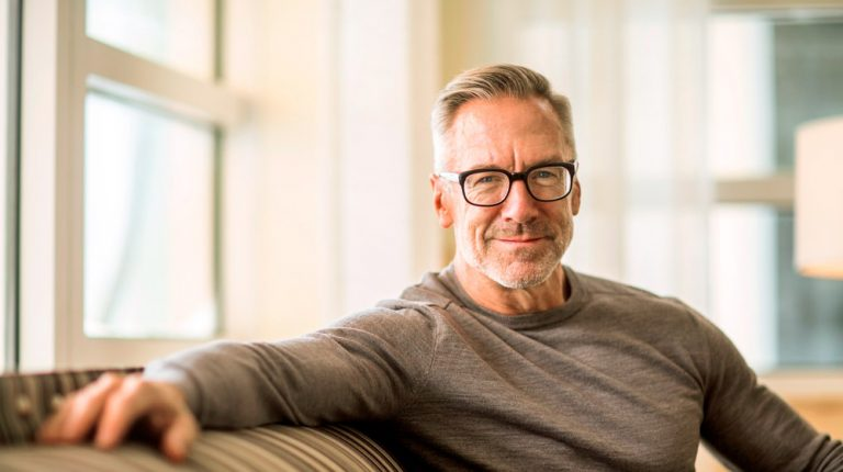 confident-mature-man-smiling-portrait-on-sofa | feature | First Signs of Hair Loss And What To Do