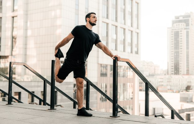 man-stretching-legs-before-workout-outdoors | HOW TO GET MORE ENERGY | EXERCISE,-BREATHE,-SWEAT