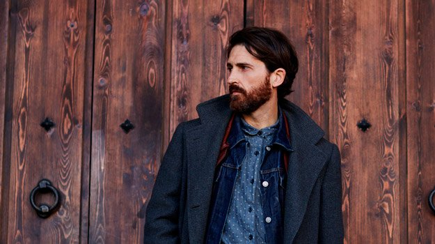 middle-aged-bearded-man-with-luscious-hair-portrait-in-front-of-wooden-wall   First Signs of Hair Loss And What To Do