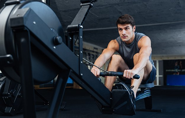 Man using rowing machine in the gym   Low Impact Exercises That Keep You Fit