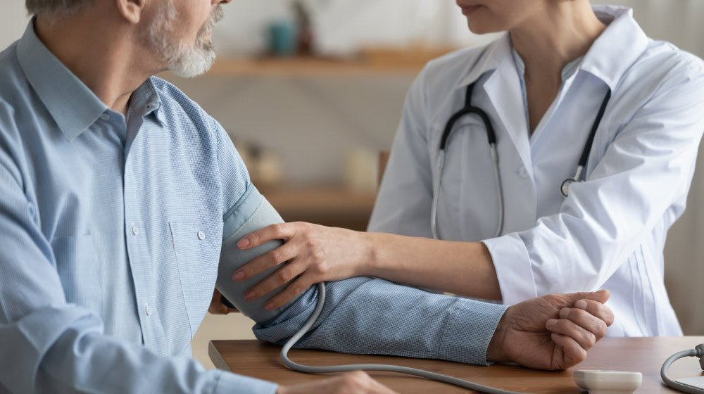 doctor-gp-physician-measuring-blood-pleasure-of-ma…ods-to-Lower-Blood-Pressure- | _feature | Eat These Foods to Lower Blood Pressure