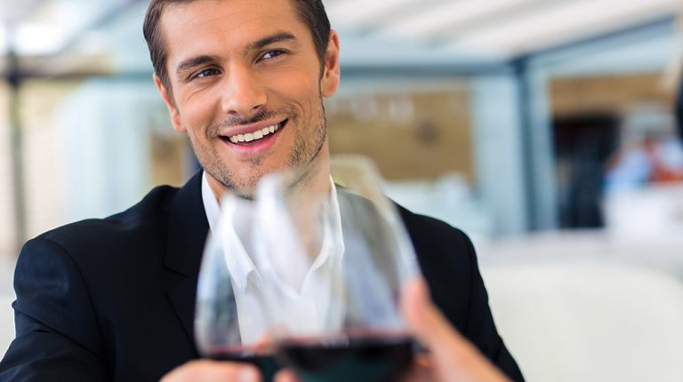 A business man holding a glass of wine | Feature | Why Alcohol Hinders Weight Loss