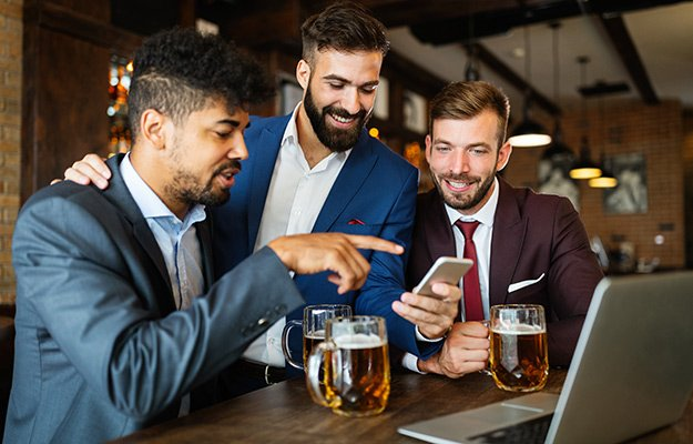 A group of business men drinking beer, looking at phone and laptop | Why Alcohol Hinders Weight Loss
