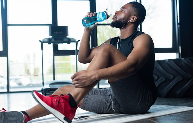 A man doing exercise drinking water | 12 Interesting Reasons You Need To Drink More Water