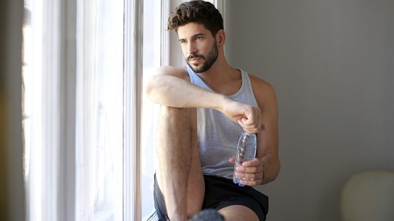 A man looking out of the window holding a bottle of water | Feature | Six Correct Key Weight Loss Hormones to Optimize Weight Management
