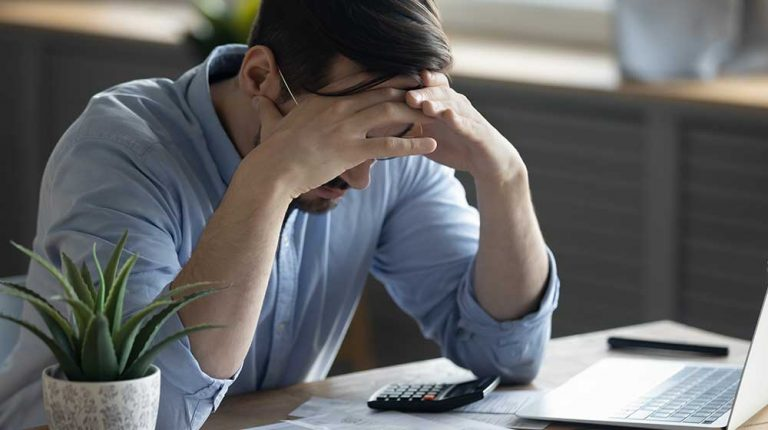 Distressed-young-Caucasian-man-sit-at-desk | feature | What's the Connection Between Stress and Weight Gain?