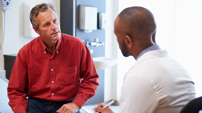 Male-patient-and-doctor-having-consultation-in-hospital-room-ss-feat | 9 Preventive Health Screening Tests For Men