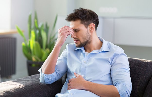 Man On Sofa Having Headache and stomach-ache-stress and sleep health | 10 Deadly Disruptors to Your Gut Microbiome