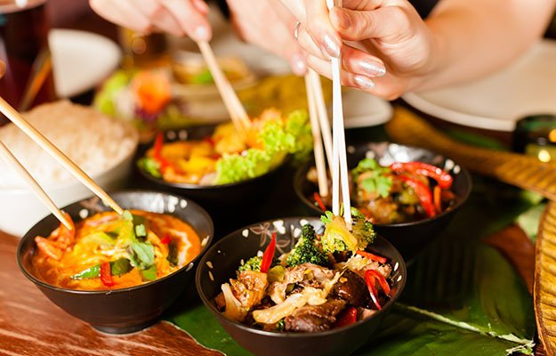 people eating in a Thai restaurant, they eating wi… chopsticks, close-up on hands and food-travel | 10 Deadly Disruptors to Your Gut Microbiome
