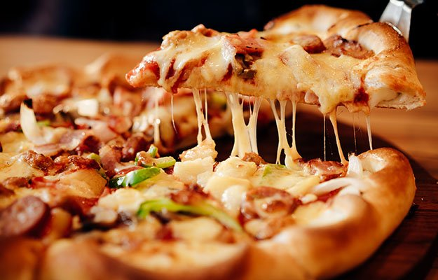 slice of pizza on wooden board-too much comfort food | 10 Deadly Disruptors to Your Gut Microbiome